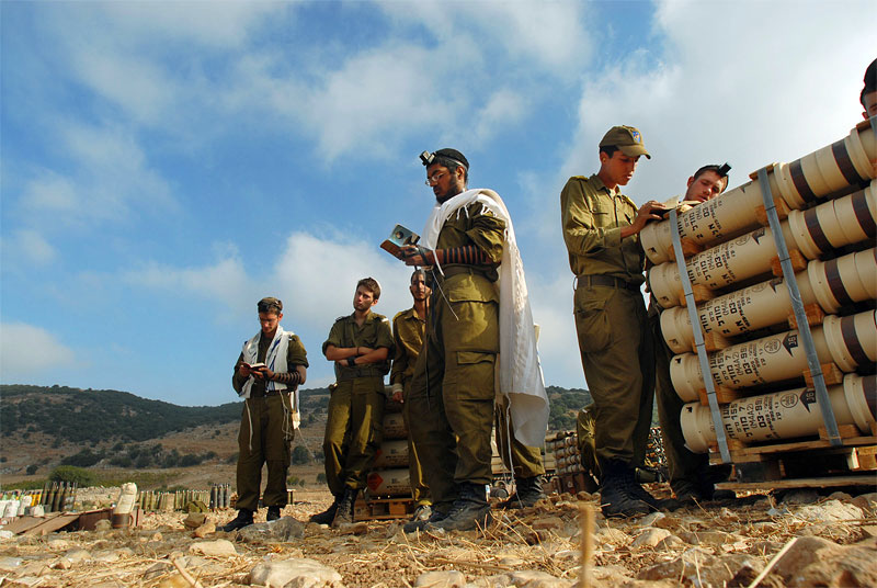 Israeli soldiers pause from tank firing at dawn to pray at an artillery camp along the Israel Lebanon border, in Israel, July 25, 2006.  Civilians on both sides of the war continue to die as Israeli troops continued their air and ground assault across Lebanon and Hizbollah fighters continue to send rockets into Israel.