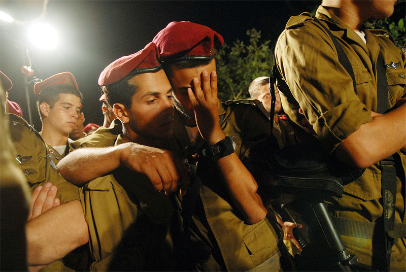 Friends and family of an Israeli soldier who was killed in Bint Jbail yesterday along with seven other soldiers weeps alongside friends and family after his buriel in Haifa, Northern Israel, July 27, 2006.  As the war between Lebanon and Israel moves into its third week, hundreds of civilians and dozens of fighters have been killed and injured on both sides.
