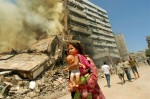 Lebanese walk through the destruction in Beirut's southern suburbs on the first day of the ceasefire between Israel and Lebanon, August 14, 2006.  Eyes around the world are on Israel and Lebanon as civilians go back to their homes for the first time since the start of the war over a month ago.