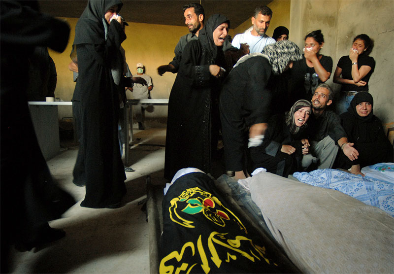 Relatives and close friends of eleven members of two families who were killed in Israeli attacks during the war weep over their bodies before a funeral in the village of Halousia village in Southern Lebanon, August 16, 2006.  The procession of funerals continues throughout the south as families begin to unearth and claim bodies from the rubble.