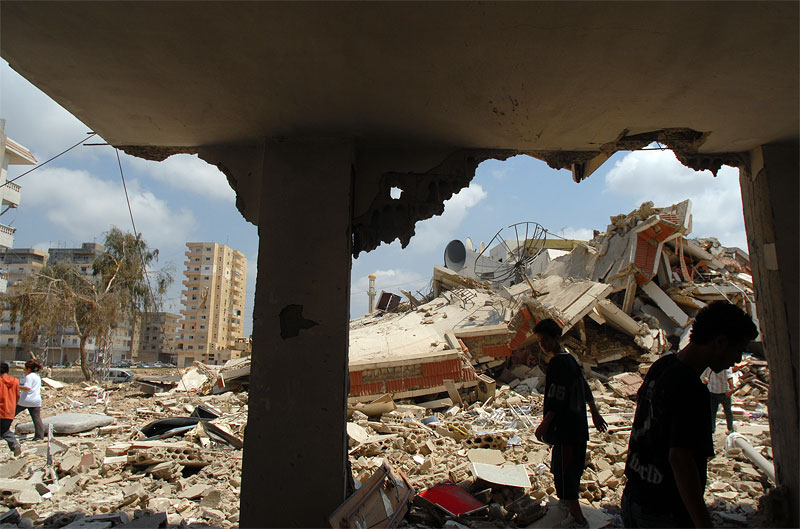 Locals walk through the rubble where Israeli paratroopers came into Tyre and faught a fierce battle with Hizbollah fighters in Tyre, Southern Lebanon, August 16, 2006.  The procession of funerals continues throughout the south as families begin to unearth and claim bodies from the rubble.