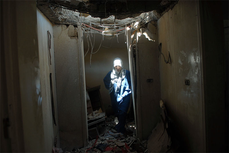 A Lebanese woman walks through the remnants of her home as it was left by Israeli troops who had been occupying it in the village of Taibe, in Southern Lebanon, August 23, 2006.  Two Lebanese men were allegedly detained and not yet released by Israeli troops as they passed through an Israeli checkpoint between two Lebanese villages,Taibe and Qantara, as Israelis once again violated the tenuous ceasefire between the two countries.
