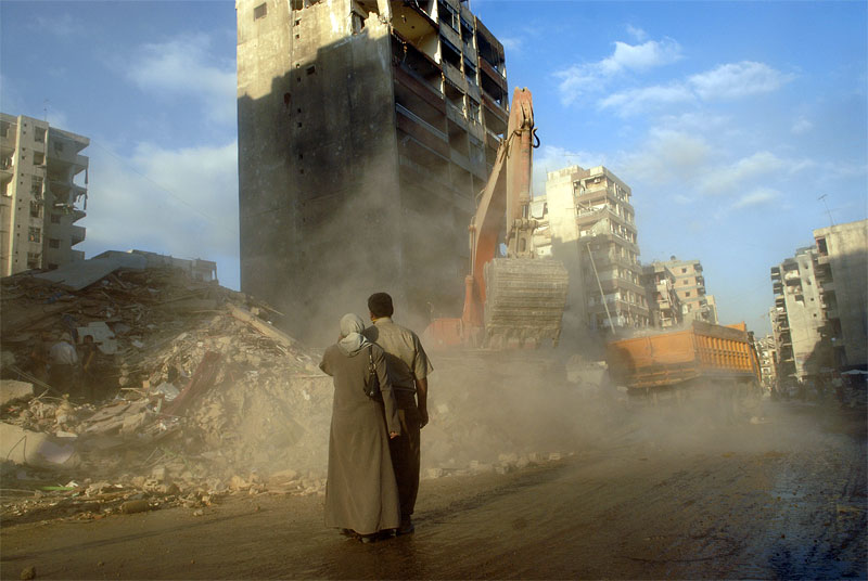 Mustafa Olwan and his wife Fatima Asadi, await the remains of their apartment in the destruction in Beirut's southern suburbs as workers clean up debris and clear roads throughout the neighborhood, August 30, 2006.  Lebanese families are still returning daily to the detroyed neighborhood to watch buildings be unearthed floor by floor, as they wait for their floor to appear to reclaim what belongings still remain.