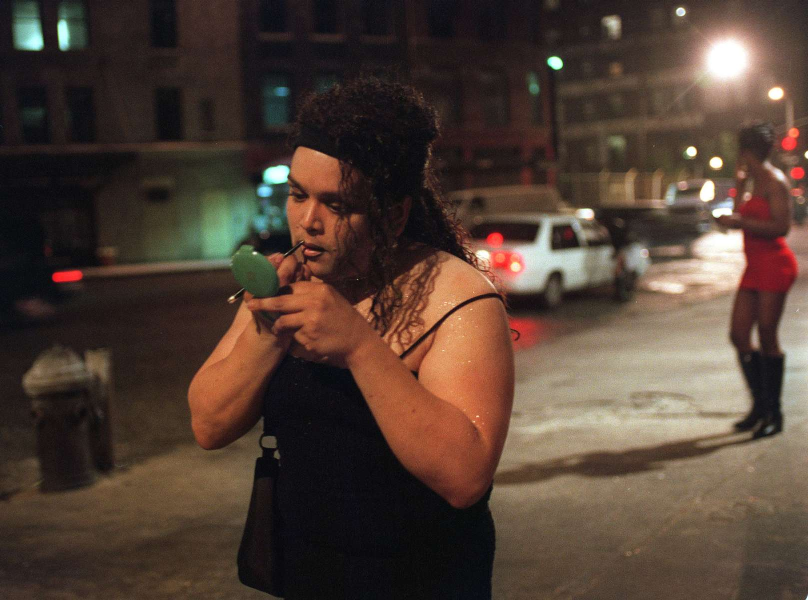 Lily Colon re-applies her mae-up as she works the stroll in the West Village's meat-packing district in New York.  August 1999.