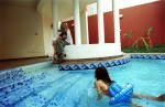 Muna Abu Sulayman sits around her pool with her two daughters in Riyadh, Saudi Arabia, October 2003