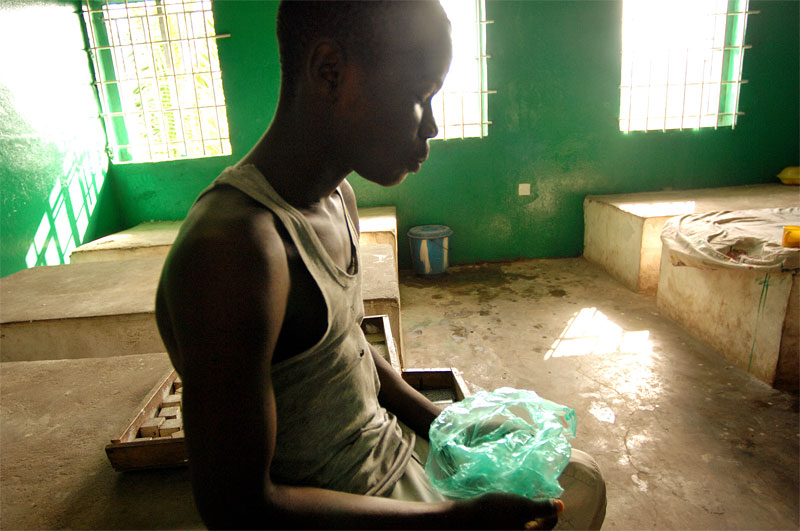 A boy convicted of larceny eats out of a plastic bag in the Kingtom emand home for juveniles in Freetown, Sierra Leone, November 22, 2006.  Freshly rennovated, the Freetown remand home remains almost empty due to poor security and few resources for food and hygeine--most of the juveniles routinely escape-- forcing the Magistrate of the juvenile court in Freetown to send most juveniles with serious offendences to prison.  Dozens of suspected juveniles are mixed with adult prisoners in prisons throughout Africa, but because of a lack of birth certificates, it is difficult for officials to ascertain who are juveniles, and who are adults.