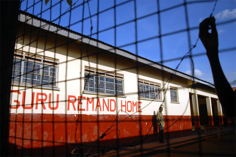 A young man stands in a courtyard of the remand home for juveniles who are awaiting trial for crimes in Kampala, Uganda, November 17, 2006.  Uganda has one remand home, and one rehabilitation home, a home for juveniles who have been convicted of crimes, in Kampala.   Across Africa, dozens of suspected juveniles are mixed with adult prisoners in prisons, but because of a lack of birth certificates, and a gross lack of resources for separate facilities, it is difficult for officials to provide separate facilities for children from adults.