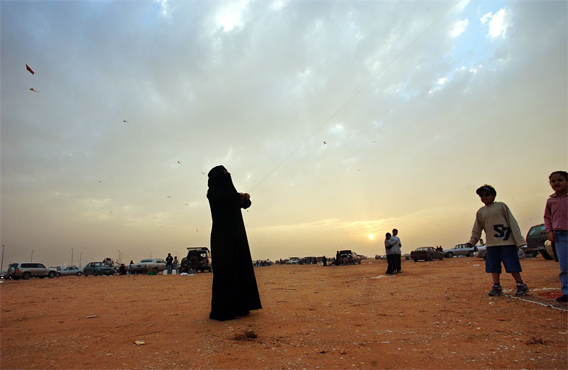 A Saudi woman flies a kite in the desert outside of Riyadh, Saudi Arabia.  2003
