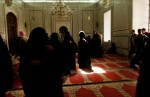 Syrian covered women walk through a shrine in a mosque in the old souk.