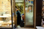 A Syrian woman sits beneath a photo of the Syrian president Assad in the old souk in Damascus. April 2006