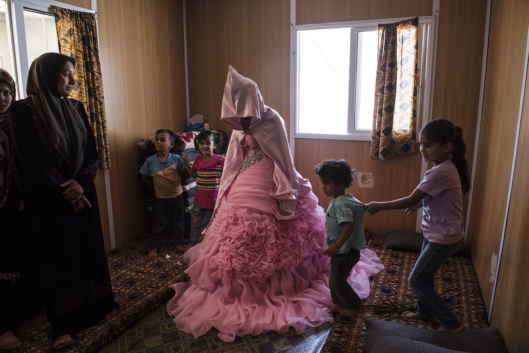 Rahaf Yousef, 13, a Syrian refugee from Daraa, poses for a portrait in her family's trailer as she is surrounded by female relatives on the day of her engagement party at the Zaatari refugee camp in Jordan, August 29, 2014. Rahaf will get married to another Syrian refugee, Mohammed, 18, in about 20 days.  While marriage under the age of eighteen was a common Syrian tradition before the start of the civil war, more and more Syrian girls are marrying at a younger age because of the insecurity of the war,  because many families feel the girls in their family may be sexually harassed if they are not under the care of a husband, and because of prospect of alleviating the financial burden of one more mouth to feed.