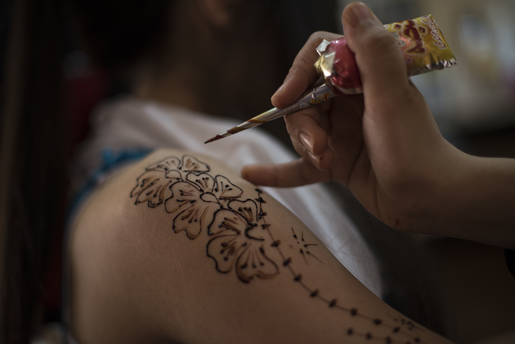 Noor, age unknown (roughly 16), is painted with traditional henna designs as she prepares for her wedding later that day in a beauty salon in the Zaatari refugee camp in Jordan, August 25, 2014. While marriage under the age of eighteen was a common Syrian tradition before the start of the civil war, more and more Syrian girls are marrying at a younger age because of the insecurity of the war,  because many families feel the girls in their family may be sexually harassed if they are not under the care of a husband, and because of prospect of alleviating the financial burden of one more mouth to feed.