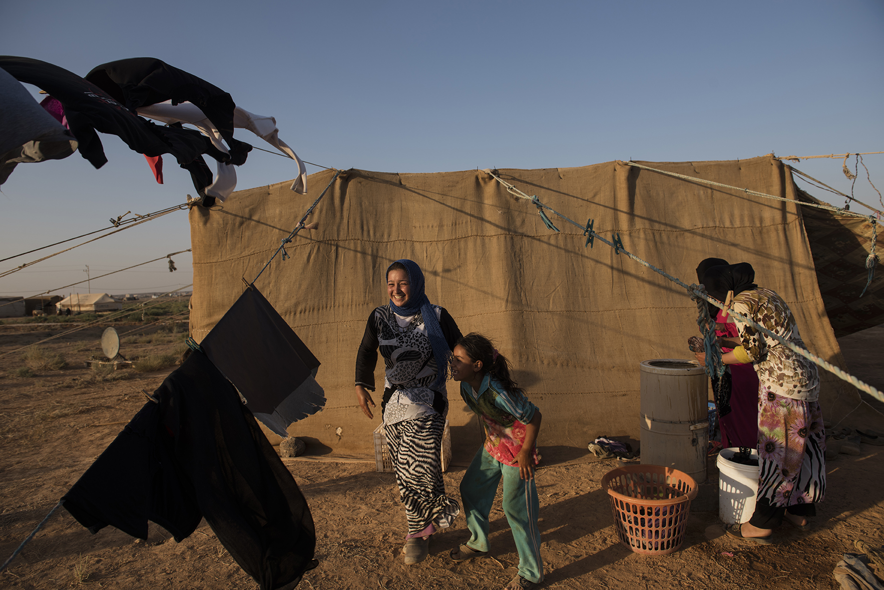 Jazia, 15, a Syrian refugee from Hama, laughs with her little sister as she washes clothes outside of her family's tent in a small camp near Zaatari camp in Jordan, August 26, 2014.  Jazia was married when she was fourteen, and divorced after seven months because her husband was physically abusive; she left him for good only a few days prior. Her mother explains that her daughter was too young to get married, but she didn't know any better, and she regrets having married her off.   While marriage under the age of eighteen was a common Syrian tradition before the start of the civil war, more and more Syrian girls are marrying at a younger age because of the insecurity of the war,  because many families feel the girls in their family may be sexually harassed if they are not under the care of a husband, and because of prospect of alleviating the financial burden of one more mouth to feed.