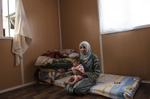 Hana Mufleh Mohammed, 16, a Syrian refugee from Daraa, poses for a portrait with her baby of 5 months at home in her trailer at the Zaatari refugee camp in Jordan, August 27, 2014.  Hana had complications with her pregnancy: she had pre-eclampsia and seizures, and spent over two weeks in the hospital unconscious after delivering. She now suffers seizures every few weeks.  While marriage under the age of eighteen was a common Syrian tradition before the start of the civil war, more and more Syrian girls are marrying at a younger age because of the insecurity of the war,  because many families feel the girls in their family may be sexually harassed if they are not under the care of a husband, and because of prospect of alleviating the financial burden of one more mouth to feed.