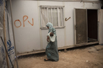 Hana Mufleh Mohammed, 16, a Syrian refugee from Daraa, leaves her trailer with her five month old baby for the clinic run by JHAS and the United Nations Population Fund at the Zaatari refugee camp in Jordan, August 27, 2014.  Hana had complications with her pregnancy: she had pre-eclampsia and seizures, and spent over two weeks in the hospital unconscious after delivering. She now suffers seizures every few weeks, and is hoping to get a referral for a neurologist to diagnose the root of her seizures.  While marriage under the age of eighteen was a common Syrian tradition before the start of the civil war, more and more Syrian girls are marrying at a younger age because of the insecurity of the war,  because many families feel the girls in their family may be sexually harassed if they are not under the care of a husband, and because of prospect of alleviating the financial burden of one more mouth to feed.