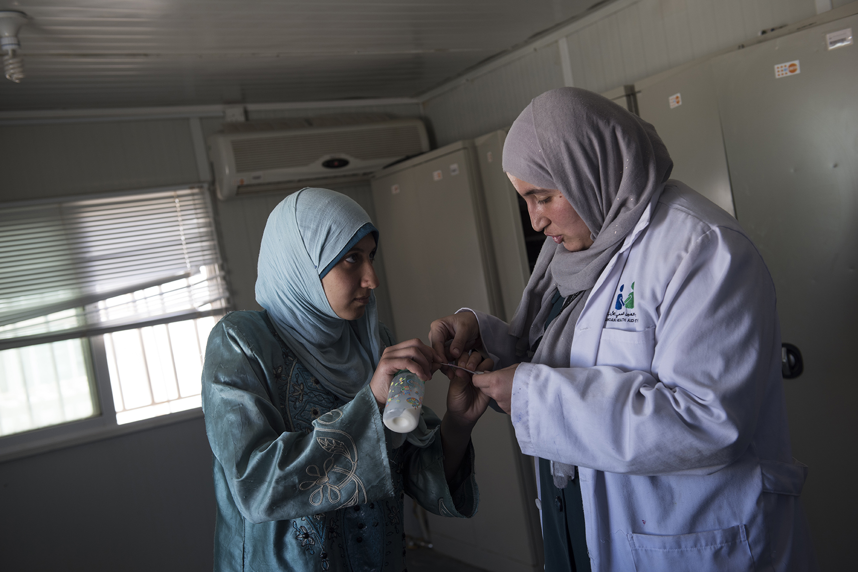 Hana Mufleh Mohammed, 16, a Syrian refugee from Daraa, speaks with midwife Nibal Shiab, 26, as she prepares to do a pregnancy test at a clinic run by JHAS and the United Nations Population Fund at the Zaatari refugee camp in Jordan, August 27, 2014.  Hana had complications with her pregnancy: she had pre-eclampsia and seizures, and spent over two weeks in the hospital unconscious after delivering. She now suffers seizures every few weeks, and is hoping to get a referral for a neurologist to diagnose the root of her seizures.  While marriage under the age of eighteen was a common Syrian tradition before the start of the civil war, more and more Syrian girls are marrying at a younger age because of the insecurity of the war,  because many families feel the girls in their family may be sexually harassed if they are not under the care of a husband, and because of prospect of alleviating the financial burden of one more mouth to feed.
