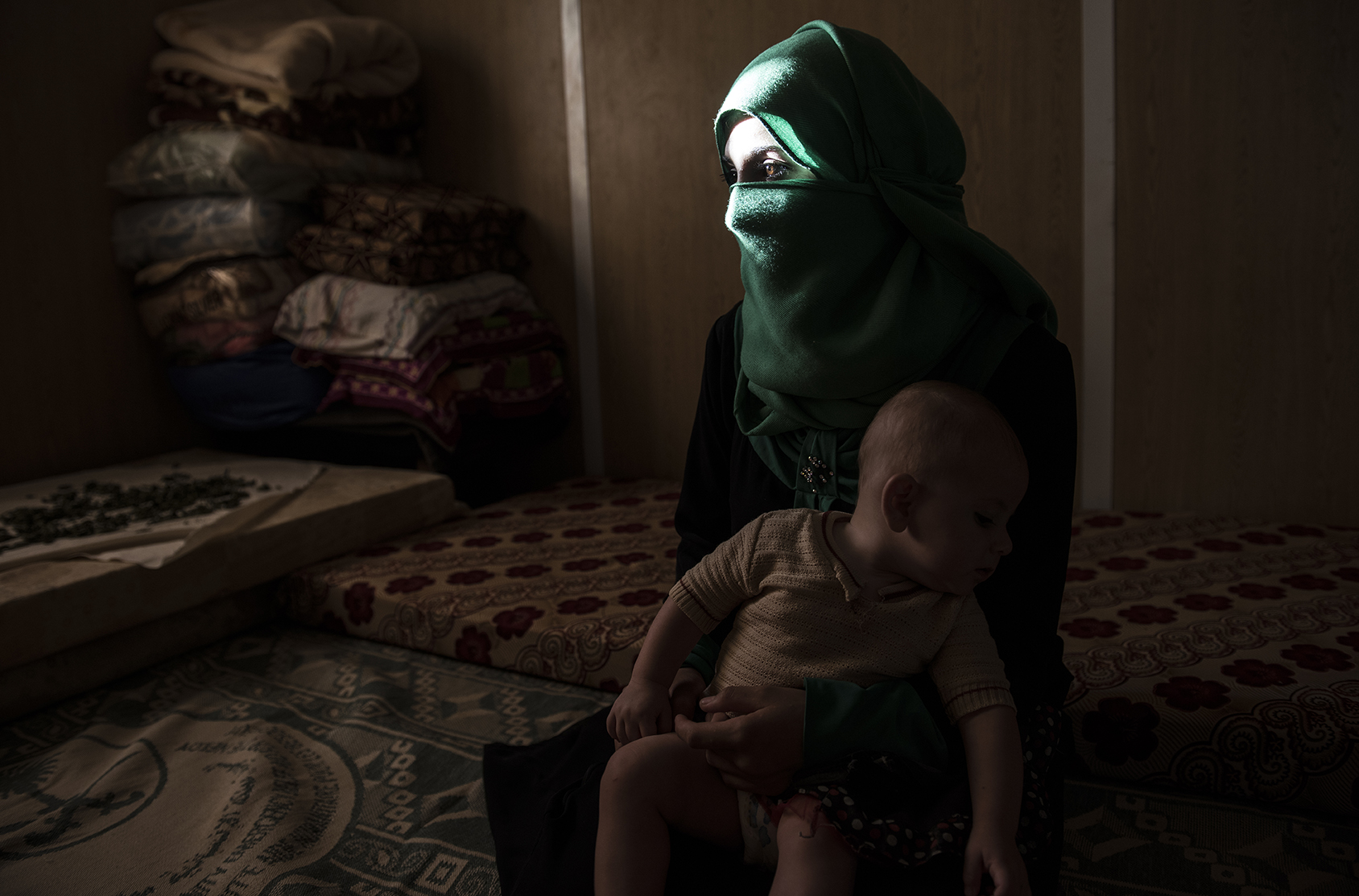 Yasmeen, 16, poses for a portrait with her baby months after leaving her abusive husband and returning home to live with her family at the Zaatari refugee camp in Jordan, August 27, 2014.  Yasmeen was married off to a 34 year-old man when she was fourteen years old, and from the first week they were married he abused her physically and psychologically, leaving her covered in blood, and with choke marks around her neck.  {quote}I expected it would be paradise,{quote} Yasmeen said referring to the marriage {quote}..I never expected he would beat me. I knew from the first time he hit me that the future was over.{quote}  While marriage under the age of eighteen was a common Syrian tradition before the start of the civil war, more and more Syrian girls are marrying at a younger age because of the insecurity of the war,  because many families feel the girls in their family may be sexually harassed if they are not under the care of a husband, and because of prospect of alleviating the financial burden of one more mouth to feed.