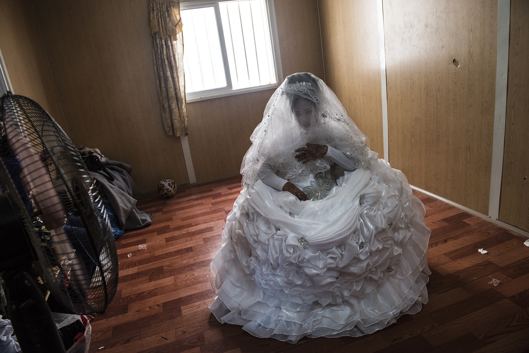 Noor, age unknown (roughly 16), awaits her groom in a beauty salon in the Zaatari refugee camp in Jordan, August 25, 2014. While marriage under the age of eighteen was a common Syrian tradition before the start of the civil war, more and more Syrian girls are marrying at a younger age because of the insecurity of the war,  because many families feel the girls in their family may be sexually harassed if they are not under the care of a husband, and because of prospect of alleviating the financial burden of one more mouth to feed.
