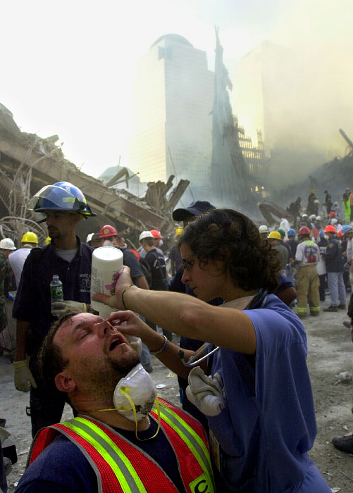 A doctor tries to wash off dust and debris from a rescue worker's eyes at the ground zero.