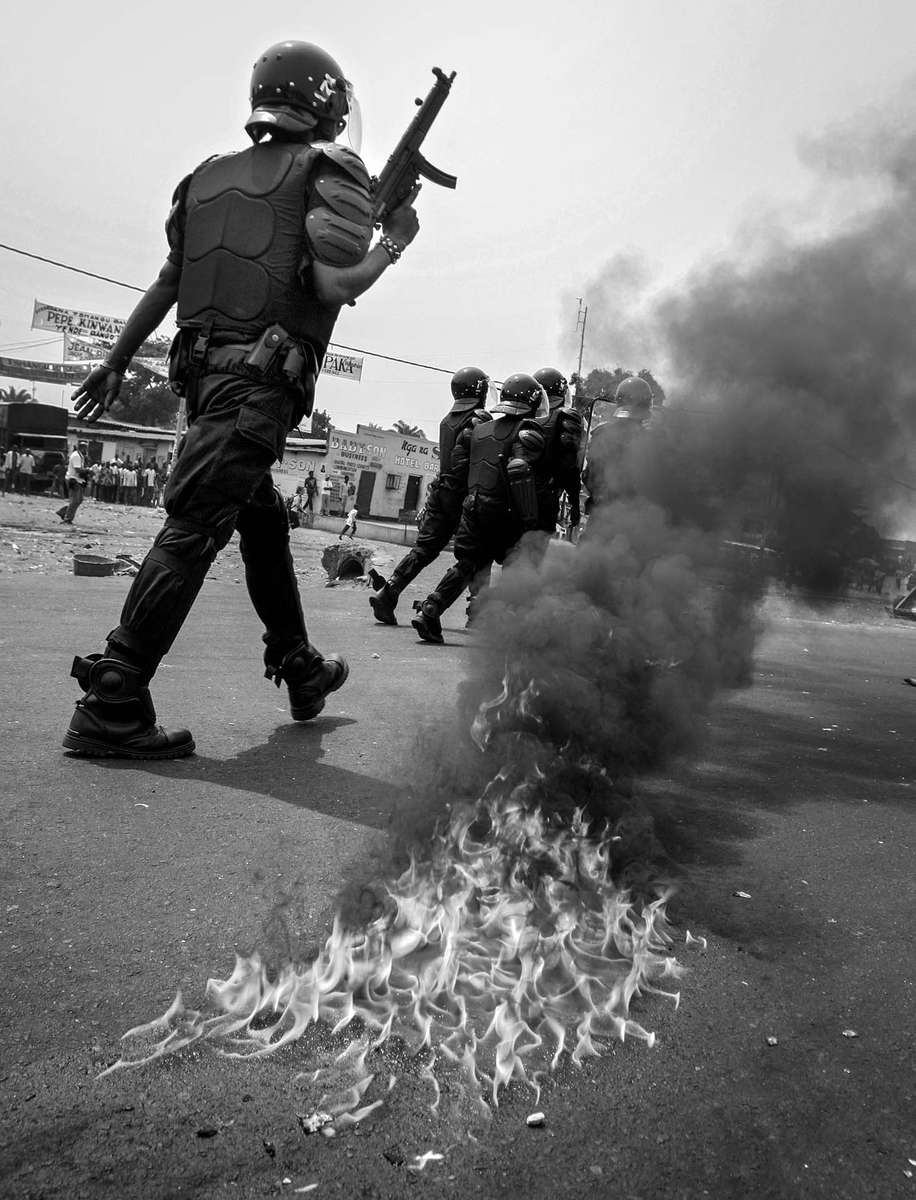 Riot police charge to the protesters past the Molotov cocktail thrown by UDPS protesters in Kinshasa.