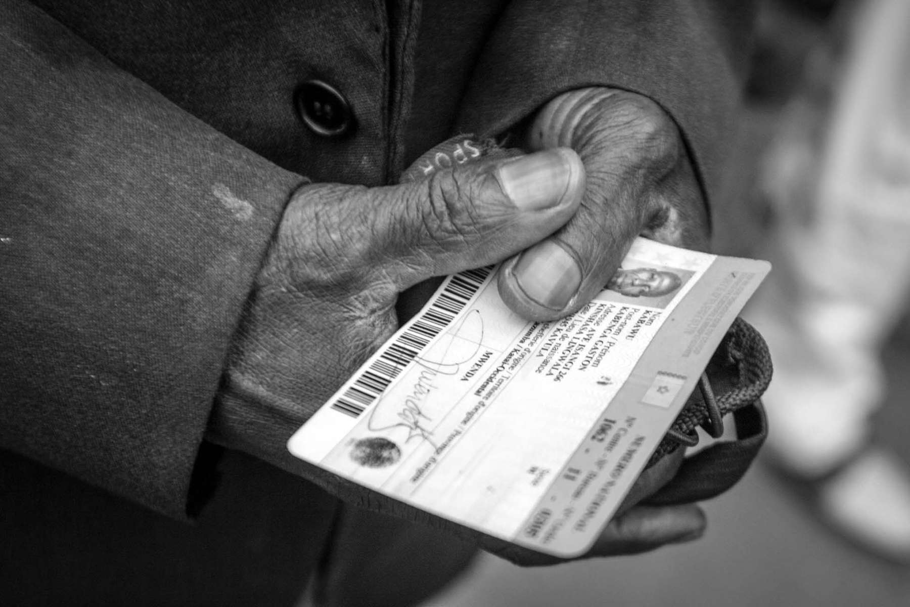 Grasping his voter registration card, Congolese man waits in line to cast his vote outside polling station in Kinshasa. For many Congolese, the voter registration card became their first piece of identification.