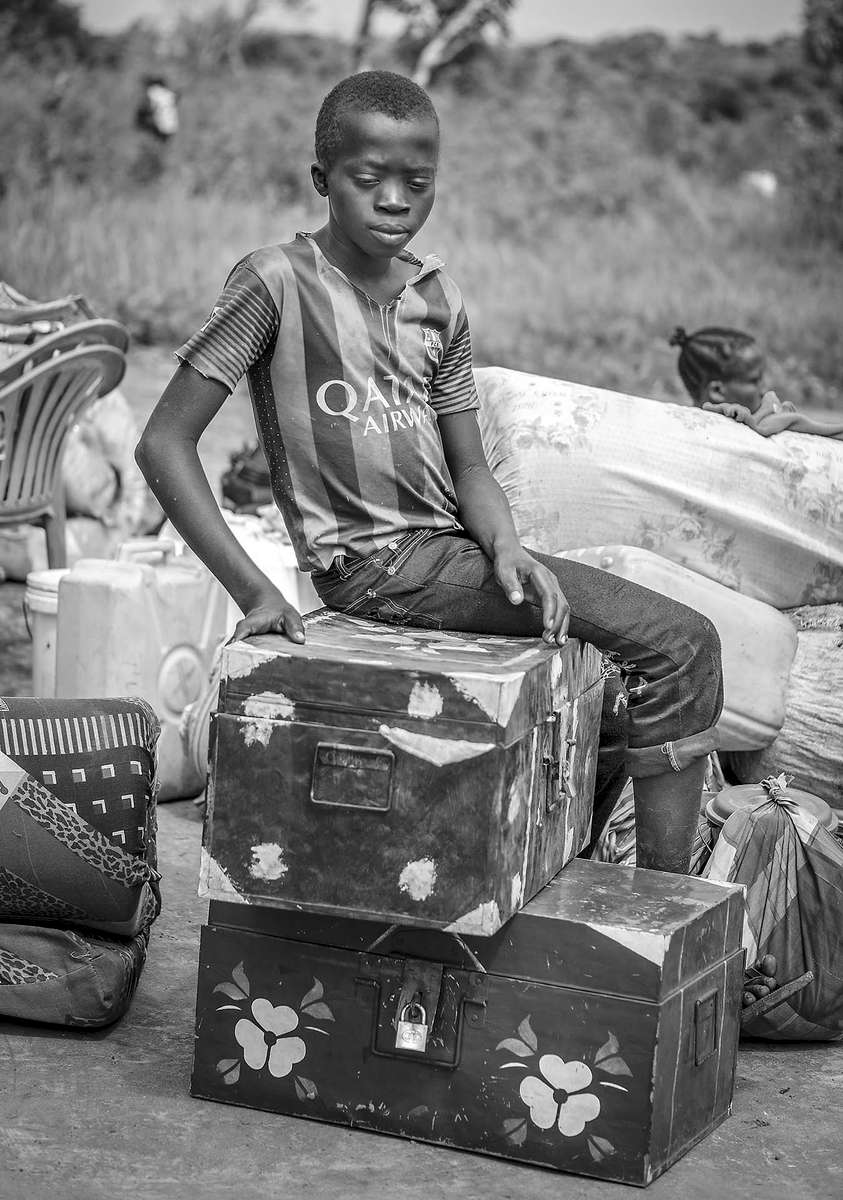Conpijas Bida, 15, guards his family's belongings while he waits for the rest of his family arrive from South Sudan at Busia crossing point in Koboko district of Northern Uganda1 May 2017. © Jiro Ose