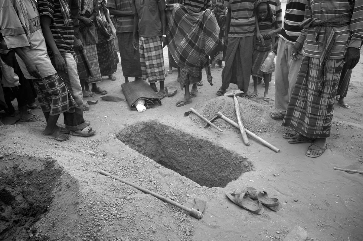 Tiny body of 1 1/2-year-old Sahro Mohammed awiats for the burial in Kobe Refugee Camp in southeastern Ethiopia, a few kilometers from Somalia/Ethiopia border, Wed. 12 August, 2011.