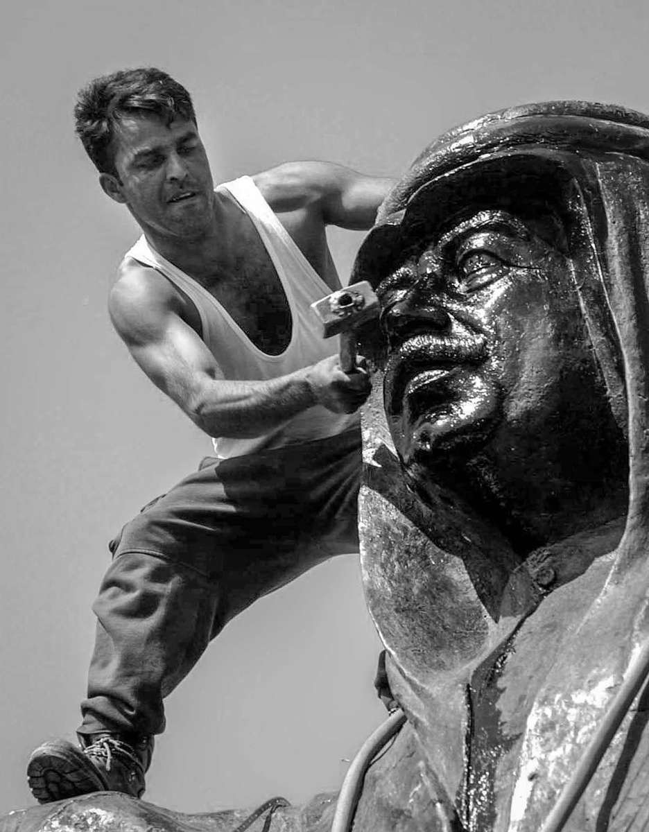 Kurdish man tries to smash the face of Saddam Hussein's statue on the day the City. of Kirkuk fell from the hand of Saddam Hussein.