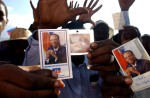 Aristide supporters hold up his pictures and show their five fingers, screaming {quote}Five More Years{quote} in Creole, meaning that Aristide should finish his term outside Presidential Pallas in Port-au-Prince.