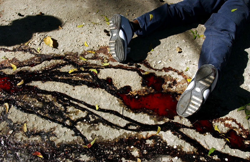 An executed body of a man suspected of being Aristide's supporter lies on the ground on the street of Port-au-Prince.