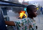 A boy rests on a burn-up car as a barricade on the street of Port-au-Prince. After the rebellion's announcement that they are marching into Haiti's capital and rumor of Aristide's departure, the capital city quickly fell into chaos.