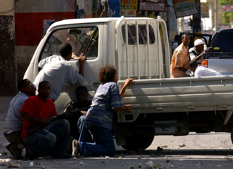 Rebel supporters and residents take cover during a gun-battle with the Shimer, armed supporter of Aristide in Port-au-Prince.