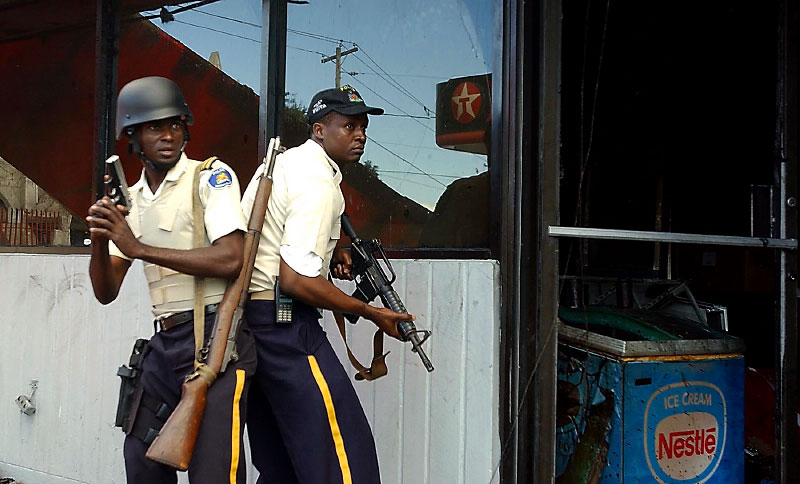 Policemen try to protect a gas station from looters in Port-au-Prince.