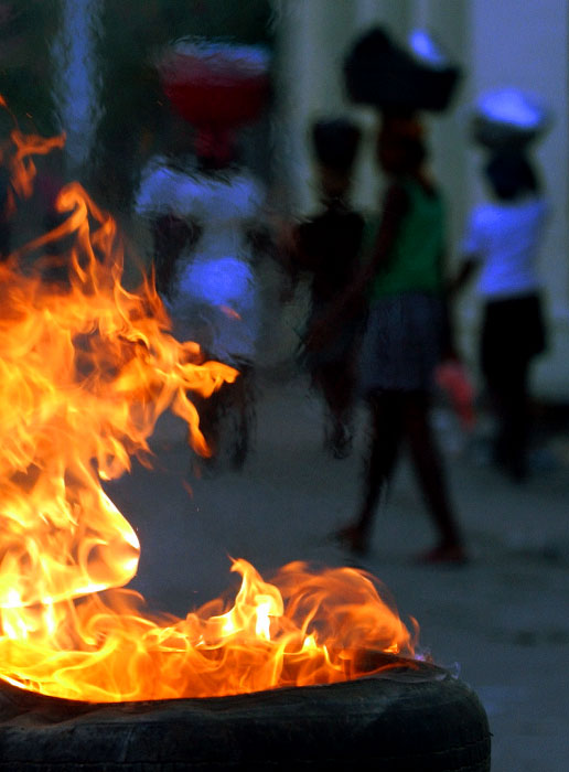 Tire burns at a barricade put up by Aristide's supporter, but life goes on in the street of Port-au-Prince.