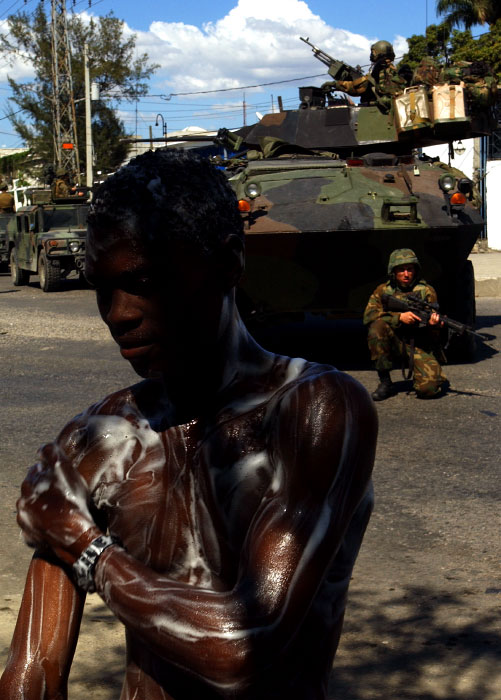 A man wash himself from on a sidewalk as U.S. Marines patrols the streets of Port-au-Prince.