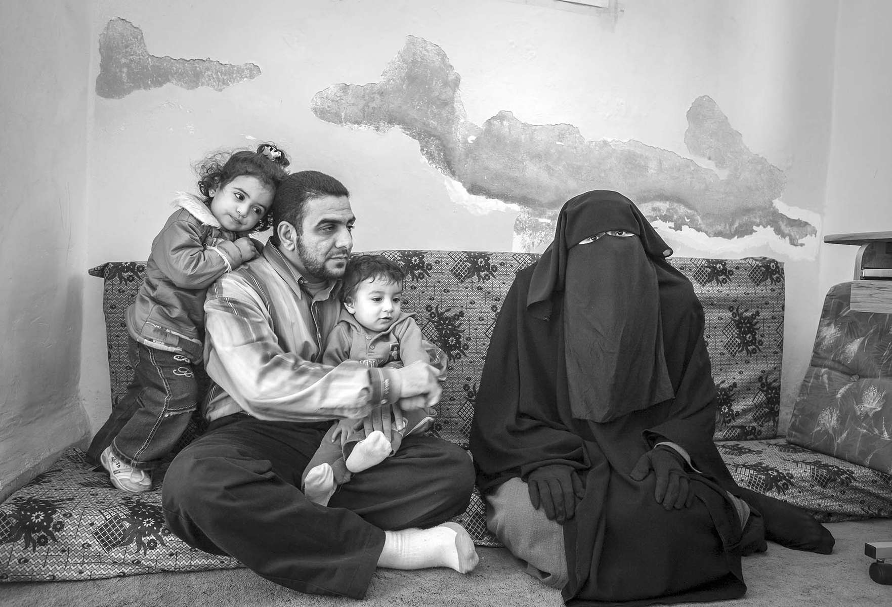 Ibrahim, his wife Adra, their two-year-old daughter Raim, and their one-year-old Salim relax at their bare and dilapidated apartment in the poor section of Amman, Jordan, November 11, 2007. Ibrahim and Adra were still newlyweds when the bloody sectarian violence in Iraq began.  Ibrahim became a Sunni when he married Adra, common practice at the time. But he did not know that the conversion had become a death sentence. When he discovered that his family was on a hit list, he made a fast and painful decision to leave.  The couple quickly said good-bye to their families and headed to Jordan. Since then, Adra's father and younger brother have been murdered.  {quote}I hate these words Shia and Sunni. They mean nothing to me other than the reason why innocent people are killed,{quote} Adra says.