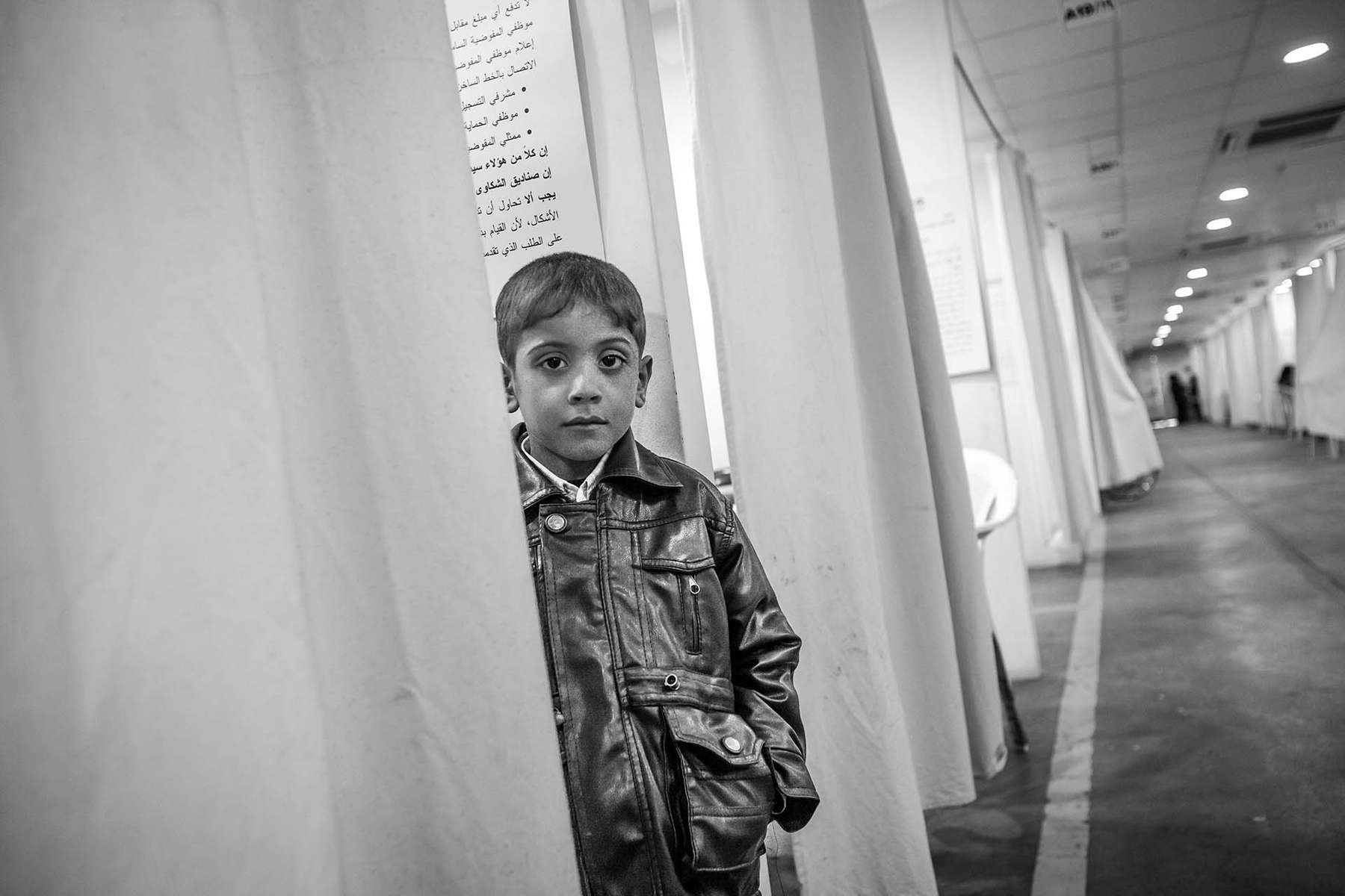 A boy waits patiently for his paretns to be interviewed at UNHCR office in Damascus.