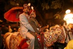 A groom makes his way to his bride on horseback in the street of Delhi.