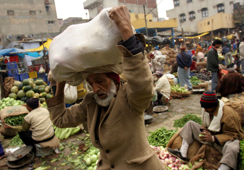 A man carries fresh produce at a vegetable market in Old Delhi in the early morning.