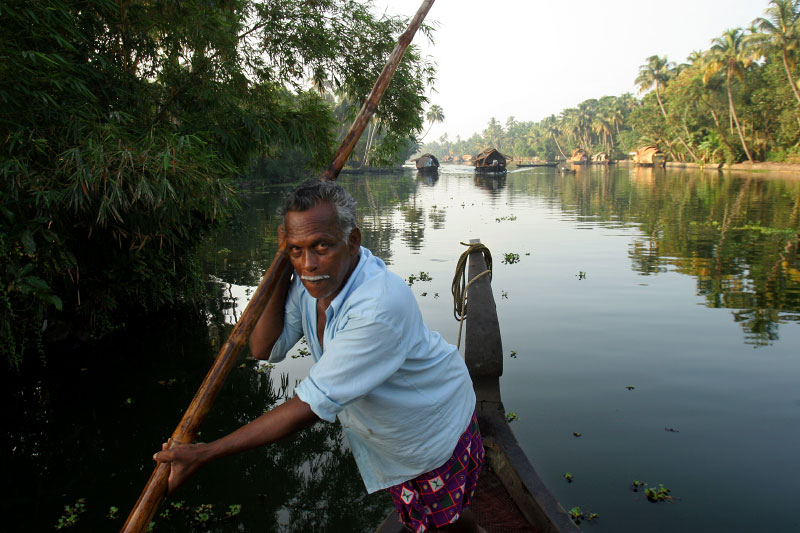 A driver of a traditional rice boat steers his way on a calm channel in Allepay, India.