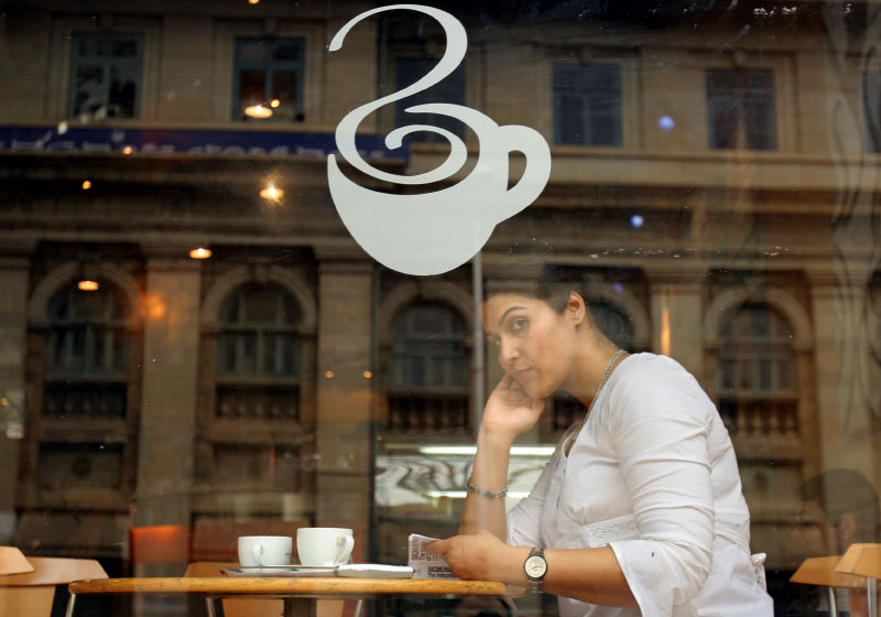 Yuppie sips cappuccino at a cafe in Bangalore, India.