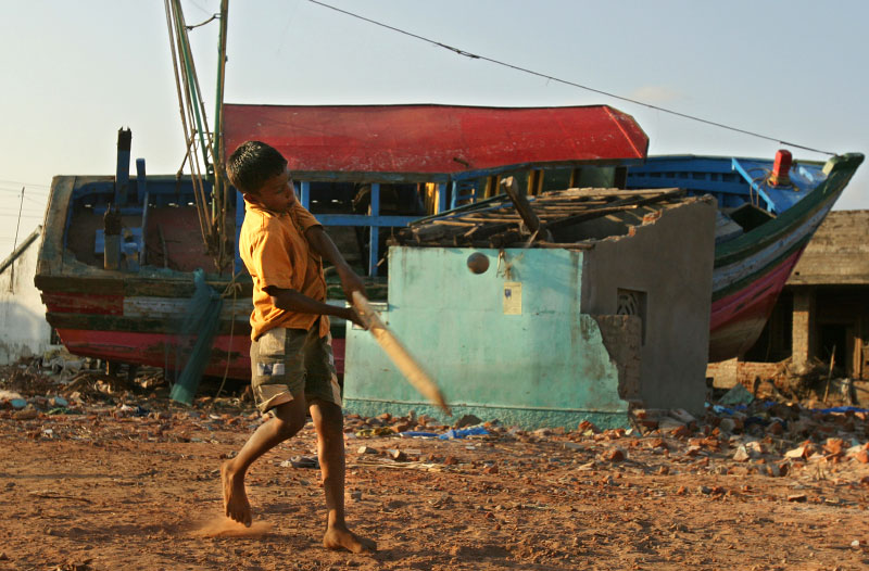 A boy plays cricket with a piece of broken ship in the afternoon.