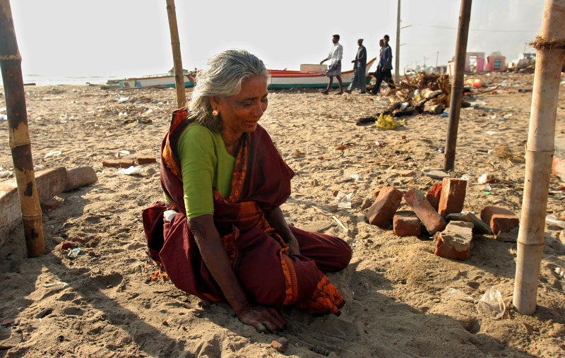 An elderly woman morns for her family members at where her house used to stand in the morning.