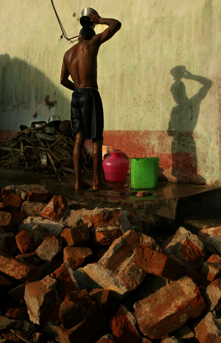 A man takes a bucket bath at his home which was destroyed by Tsunami.