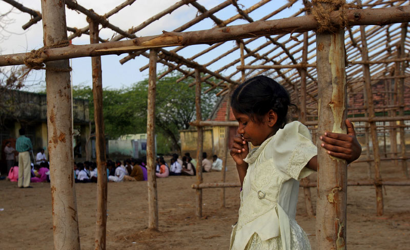 Orphan girl watches a regular class from the distance. All the orphaned children are put in the class they call counseling for orphaned children.