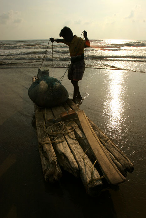 A lone fisherman gets ready to set out to the sea in the morning with his canoe patched together from broken woods.