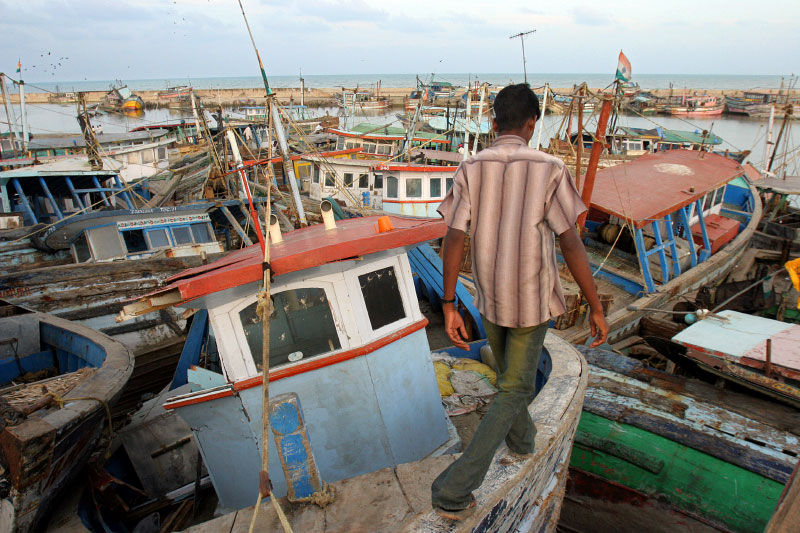 A fisherman navigate his way through a maze of destroyed boats.