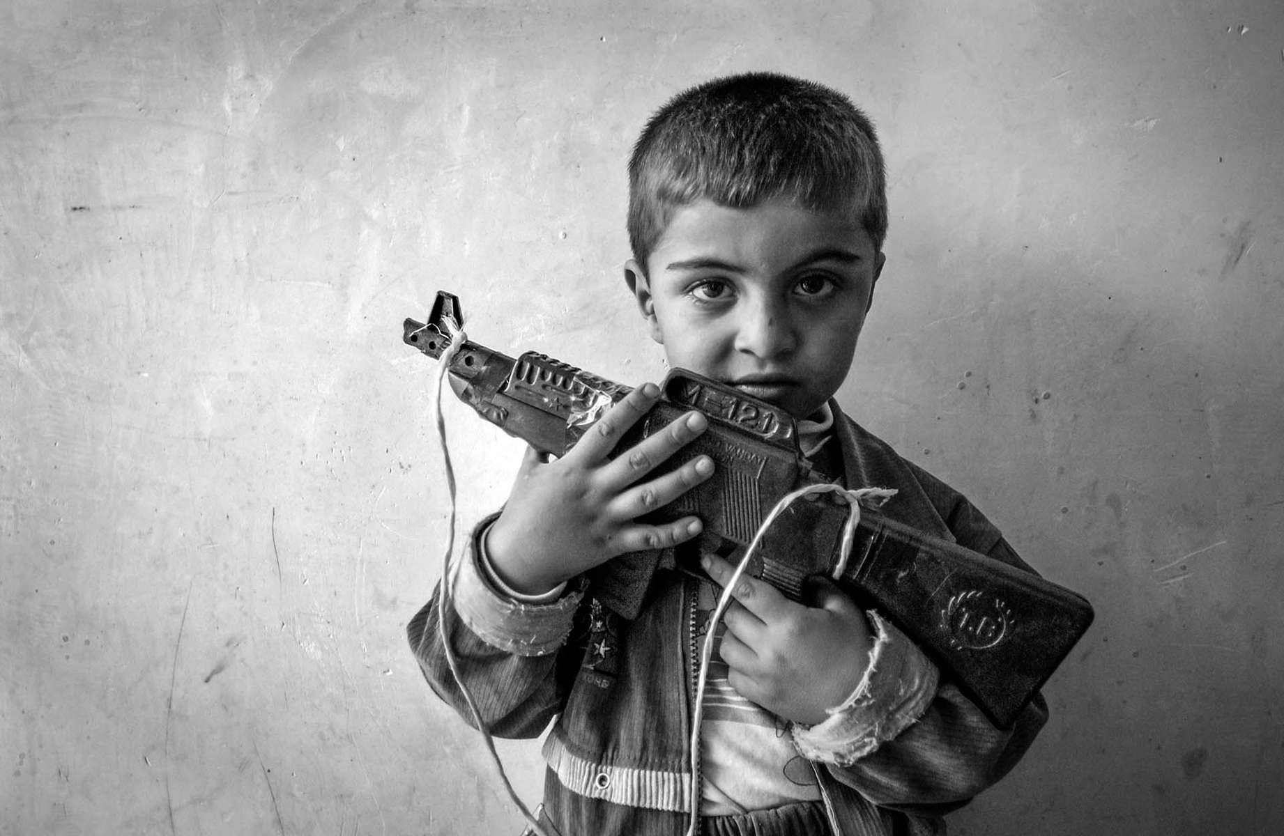4-year-old Bawan Ahmad Salih holds his toy AK-47 assult rifle at his uncle's house in border town of Kalar Monday, April 7, 2003. AK is weapon of choice for Kurdish male, and they can be seen everywhere, even at toy store.