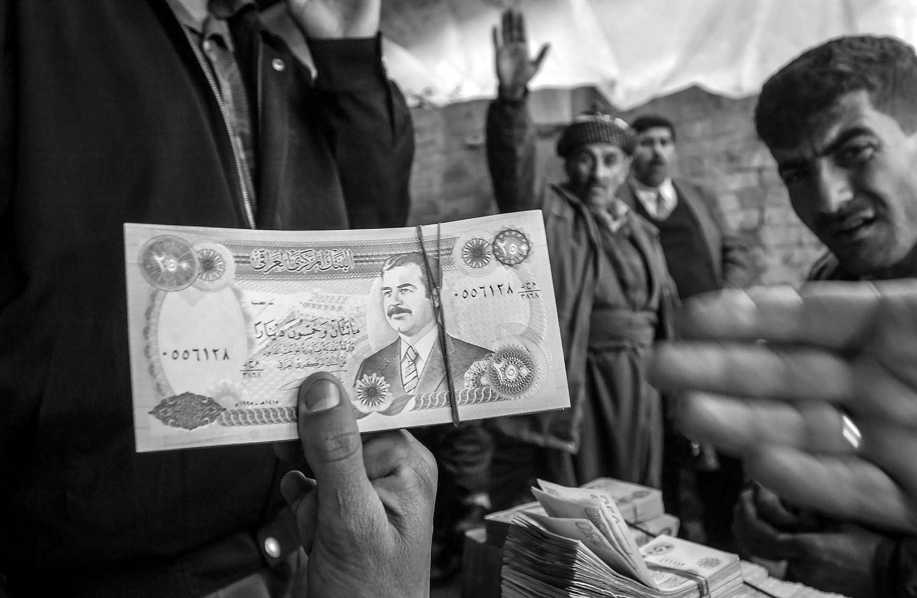 Busy money exchange market in the city of Sulymania in Kurdistan. If you are leaving Kurdistan into the area controled by Saddam, you need his money.