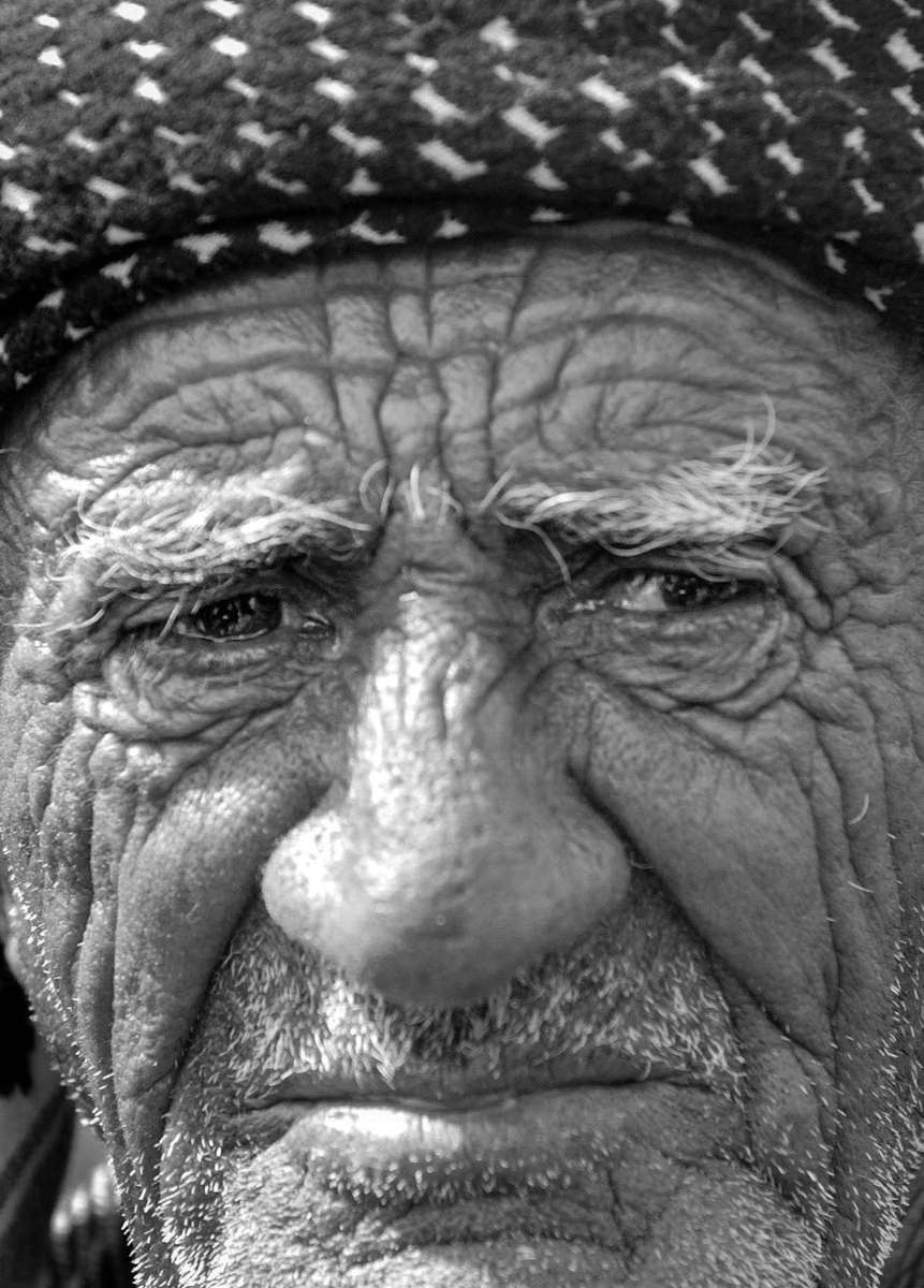 Kurdish man wares his hardship on his face as he waits to leave the village of Chamchamal, which borders the area controled by Saddam Hussain. Town residents began evacuating their houses due to the loomig war, in fear of chemical attack.